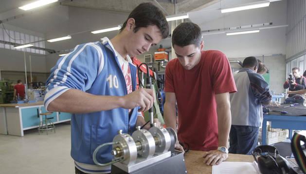 Dos jóvenes realizan prácticas en un taller.