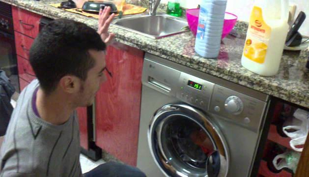 Un joven, ante una lavadora.