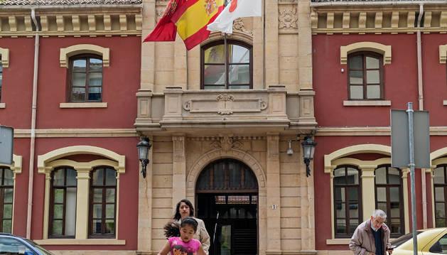 Varios transeúntes cruzan el paso de cebra peatonal frente al ayuntamiento de Estella.