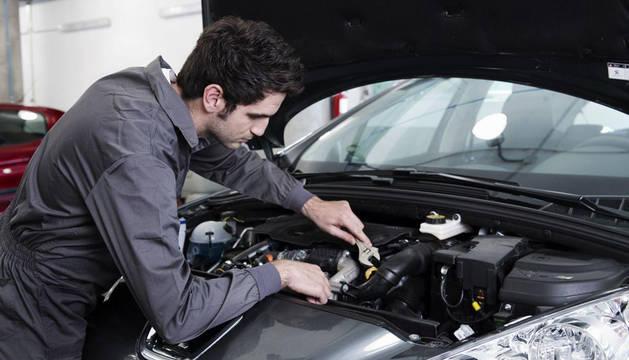 Un mecánico revisa la instalación de un  coche en un establecimiento para detectar una avería.