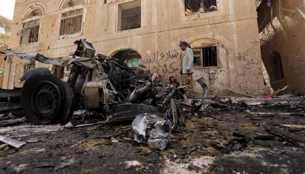 Varios yemeníes inspeccionan el lugar tras explotar un coche bomba en Saná.