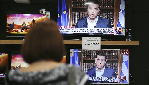 Una mujer ve en las pantallas el discurso de Tsipras.