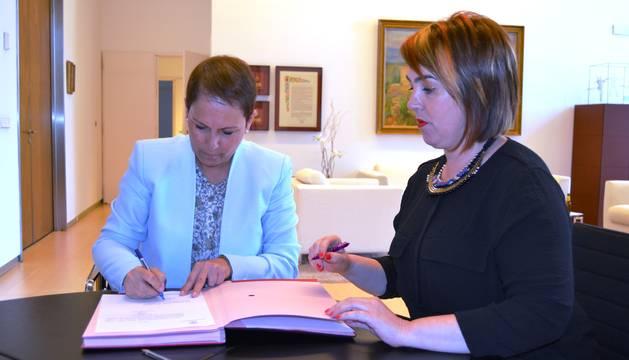 Uxue Barkos, firmando la aceptación de su candidatura a Presidenta del Gobierno, ante Ainhoa Aznárez, presidenta del Parlamento.