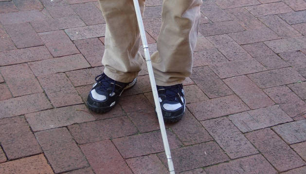 Un invidente pasea con un bastón.
