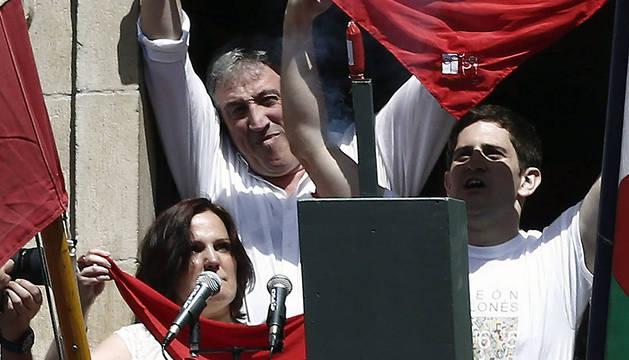 Javier Aranegui, del Orfeón Pamplonés y Chantal Estrada, nieta de un miembro de la peña La Veleta, en el momento de prender la mecha del cohete.