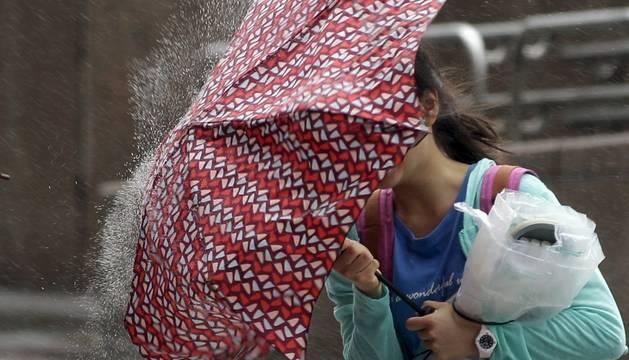 Una joven sostiene su paraguas para protegerse de la lluvia y el viento.