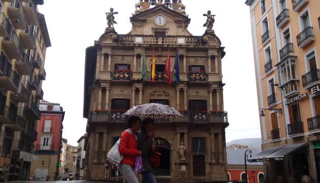 Dos personas pasean frente al Ayuntamiento de Pamplona.