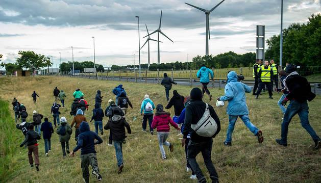 Inmigrantes se dirigen hacia el eurotúnel en Coquelles, cerca de Calais.