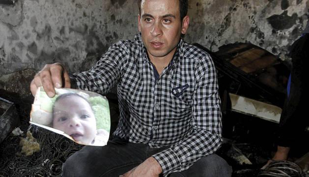 Un familiar sostiene una imagen del bebé asesinado.
