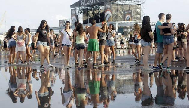 Varias jóvenes tras la tormenta registrada en la primera jornada grande del festival Arenal Sound.
