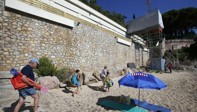 Los turistas acceden a la playa, de la que se retira el ascensor construido para el rey.