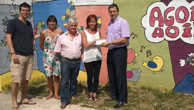 Mike Lacabe, director de la oficina de CaixaBank en Aoiz, entrega la aportación económica a Inmaculada Beroiz, directora del colegio.