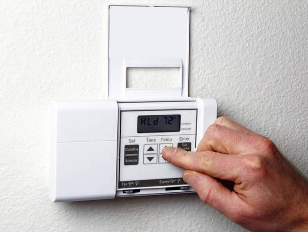 Un hombre regula un aparato de aire acondicionado
