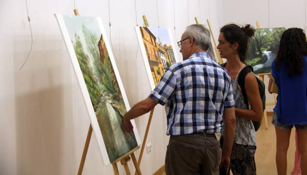 Dos visitantes miran uno de los cuadros presentes en la exposición.