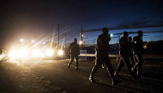 Policías franceses patrullan cerca a las vías del Eurotúnel a las afueras de Calais.
