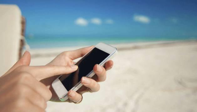 Una mujer usa el smartphone en la playa.