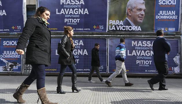 Transeúntes caminan frente a vallas con propaganda electoral en el centro de Buenos Aires.