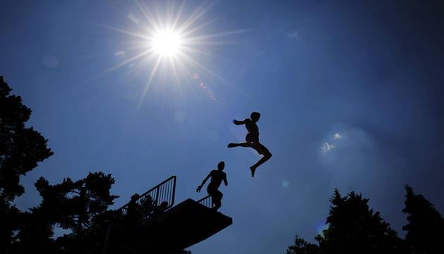 Dos jóvenes saltan desde un trampolín de 5 metros en una piscina en Grossröehrsdorf, Alemania.