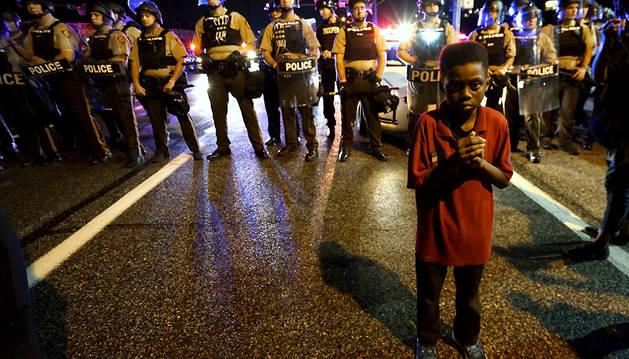 Amarion Allen, de 11 años, junto a un cordón policial antes de los incidentes en Ferguson.