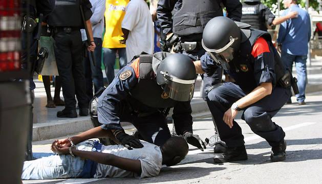 Miembros de los Mossos d'Esquadra retienen a un participante en los disturbios que han tenido lugar en Salou (Tarragona).