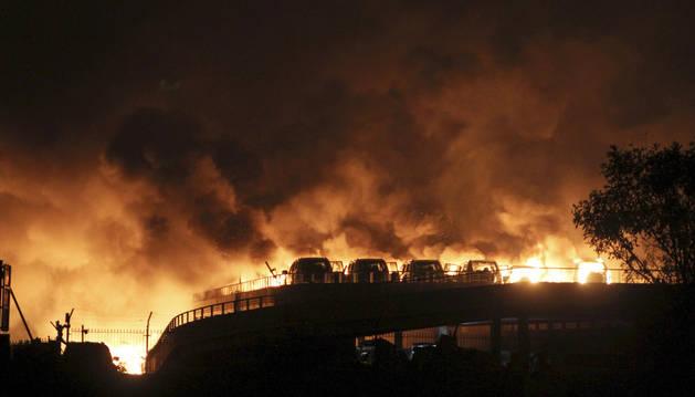 Vehículos ardiendo tras la explosión de un almacén en el norte de China.