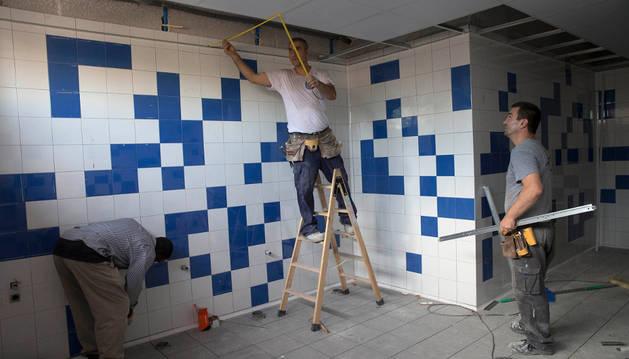Dos operarios trabajan en la mejora de los baños del colegio público Griseras.