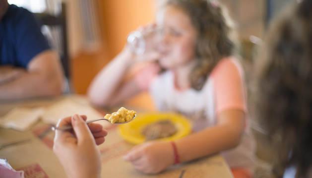 Una madre da de comer una cucharada de arroz a su hija.
