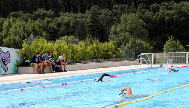 Varias personas nadan en la piscina mientras algunos vecinos de Monreal los observan.