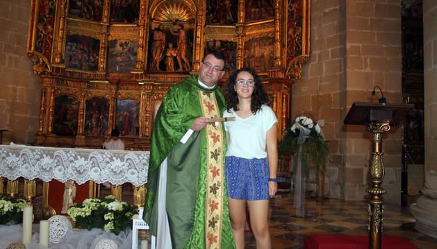 El párroco de Cintruénigo, José Ignacio Larragueta, junto a la niña Alehandra García Marín.
