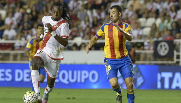 El delantero del Rayo Alberto Manucho (i) lucha el balón con Javi Fuego, del Valencia.