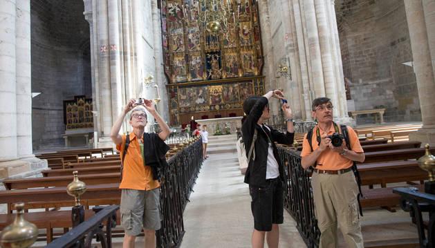Un grupo de turistas toma fotografías del interior de la Catedral de Tudela.