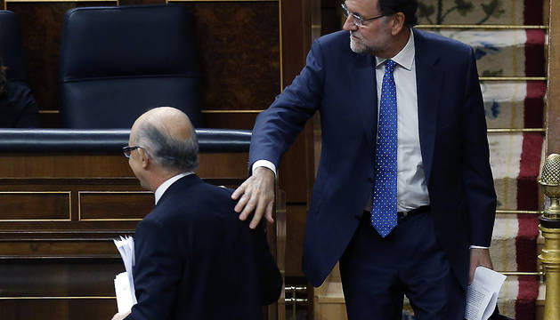 Rajoy felicita al ministro de Hacienda, Cristóbal Montoro, tras la intervención de éste ante el pleno del Congreso.