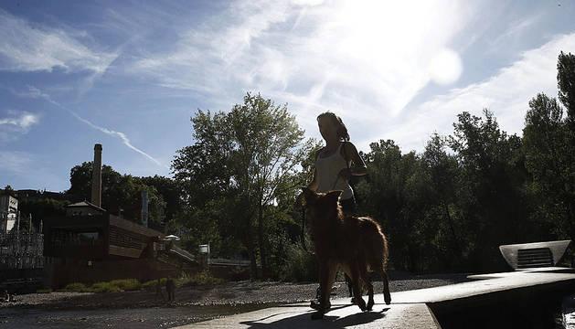 Una joven junto a su mascota en el paseo del Arga.