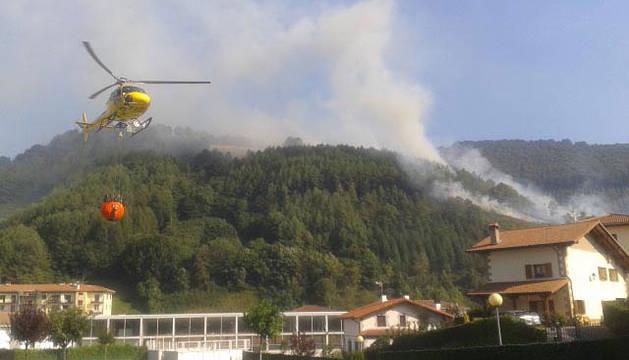 Un helicóptero recoge agua de una piscina en Leitza.