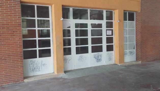 Varios de los grafitis que ayer permanecían en las puertas del colegio.
