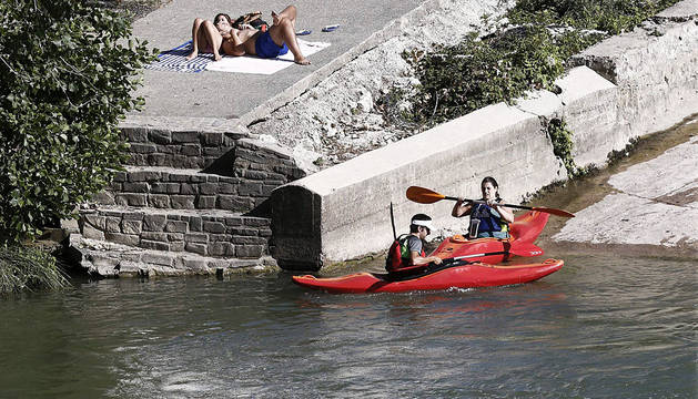 Varias personas disfrutan en el río Arga en Pamplona.
