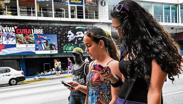 Unas chicas usan su teléfono móvil en Cuba.