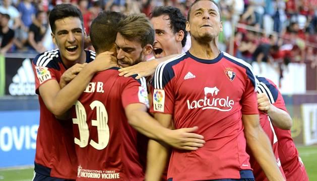 Tano hace un gesto de alegría a la grada mientras sus compañeros felicitan al goleador Berenguer.