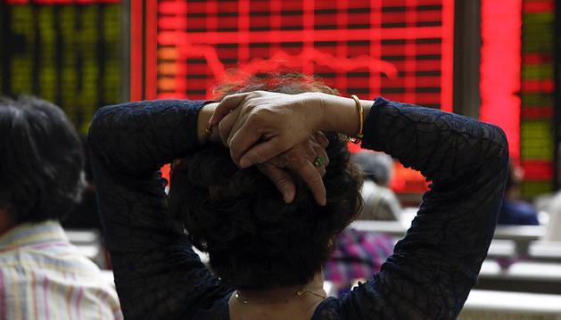 Una mujer comprueba la evolución de la bolsa de Shangái en Pekín.