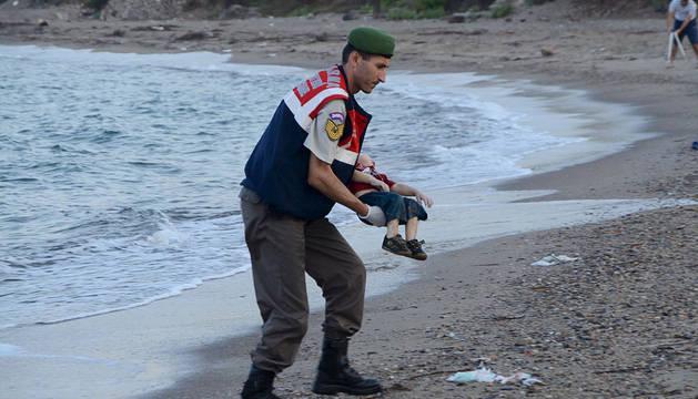 Un gendarme turco recoge a un niño fallecido ahogado en una playa turca.