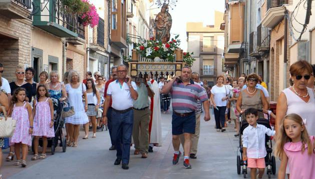 Varios vecinos portan a la Virgen del Portal ante los numerosos asistentes a la procesión del traslado.