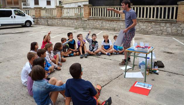 Asier Santana, monitor del taller medioambiental sobre el agua, da explicaciones a los niños.