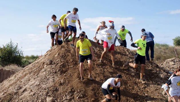 Un grupo de corredores intenta superar uno de los montículos de tierra del recorrido.