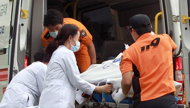 Trabajadores de los servicios de rescate trasladan el cuerpo de un fallecido.