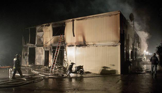Bomberos trabajan para sofocar los restos del incendio en el centro de Rottenburg.