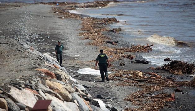Dos agentes junto al primer cuerpo, encontrado junto al agua.