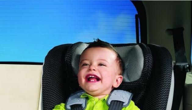 Un niño con su sillita de seguridad homologada.