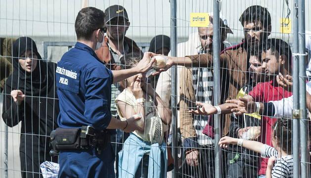 Un agente de policía reparte comida a los inmigrantes en Roszke.