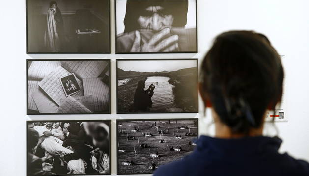 Una joven observa varias fotografías que forman parte de la exposición World Press Photo 2015.