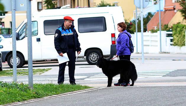 El cabo de la Policía Local, Félix Goikoetxea, con la dueña de un perro ayer en Alsasua.